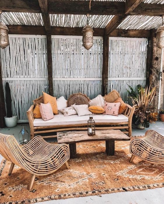 a boho tropical patio with a wooden bench and lots of pillows, catchy rattan chairs, a wooden table …