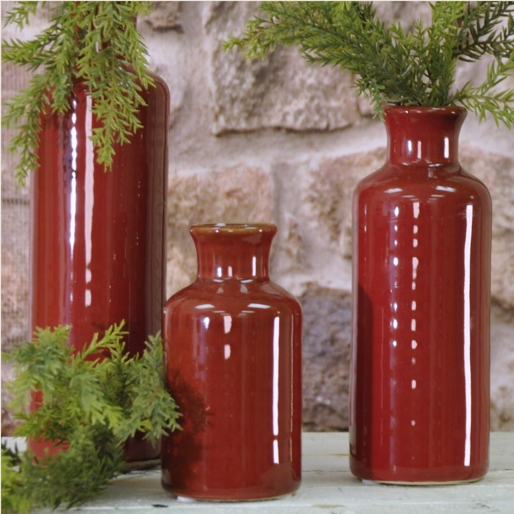 """A beautiful dark winter red color covers this set of three vases...just add your favorite wintry greens to add a festive touch to any mantle or table arrangement. Dimensions range from 5"""" X 9.5""""."""