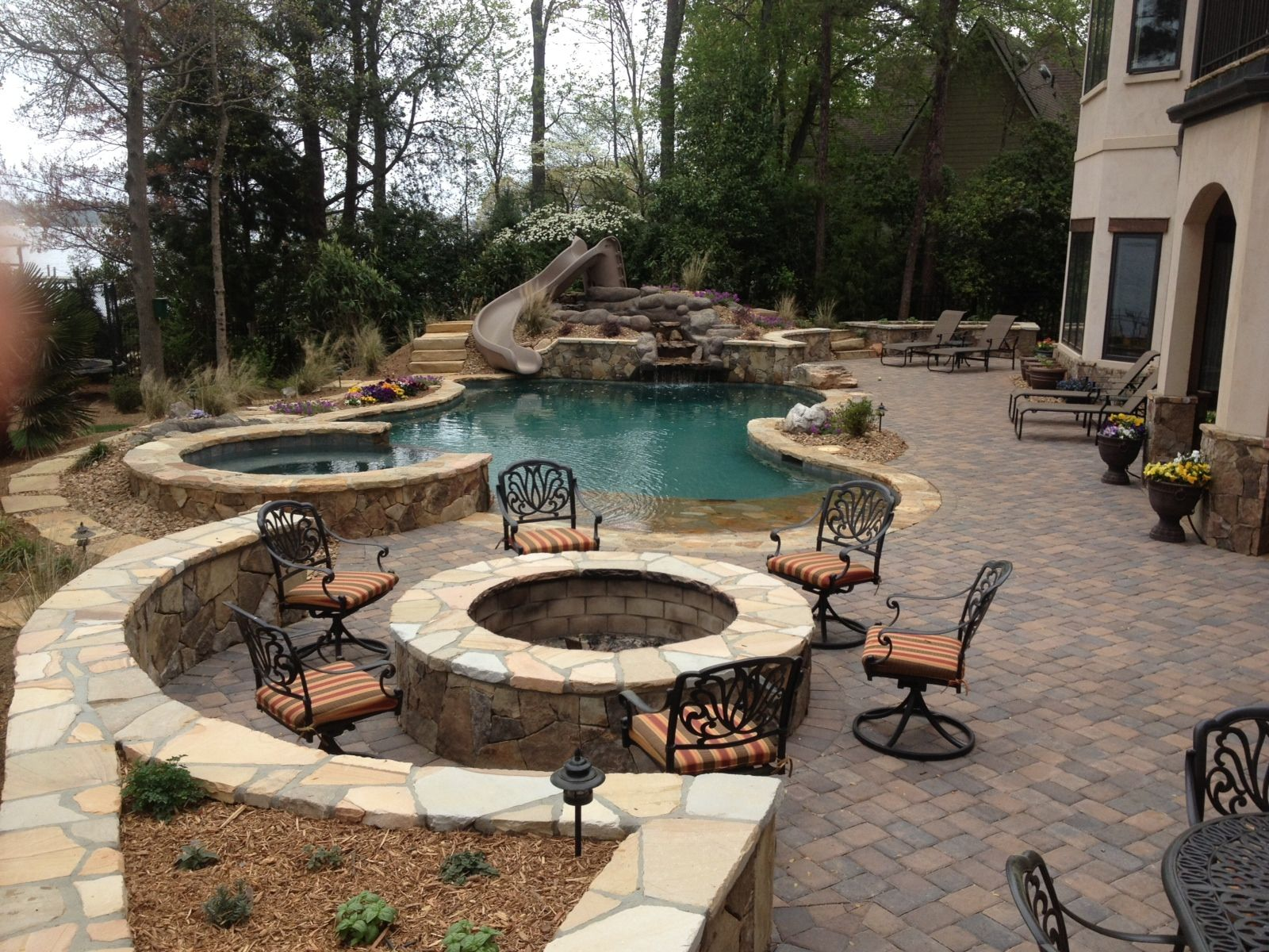 brick and stone pool deck with green tiles and black bow back