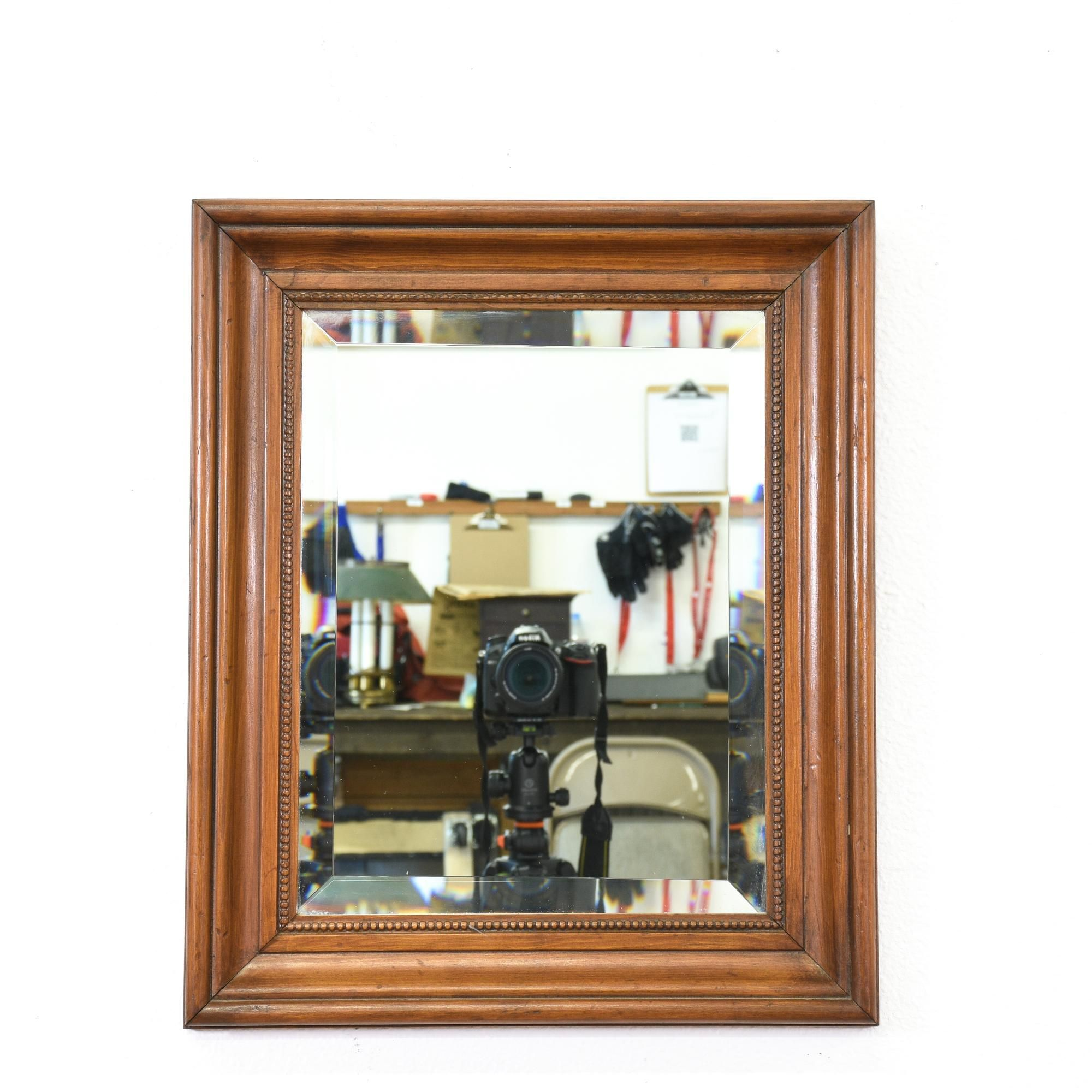 This framed mirror is featured in a solid wood with a ...