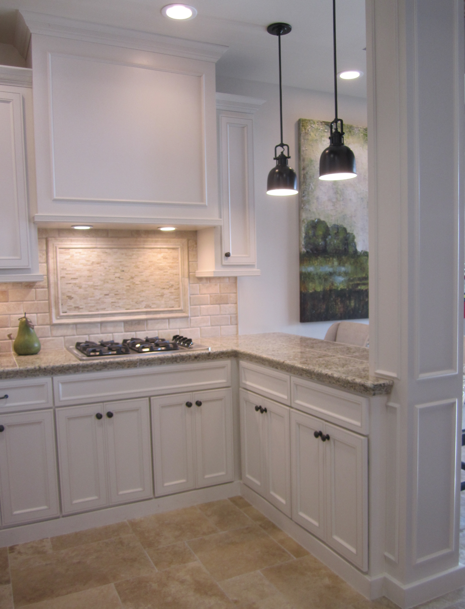Kitchen with off white cabinets stone backsplash and for Pictures of white kitchen cabinets with granite countertops