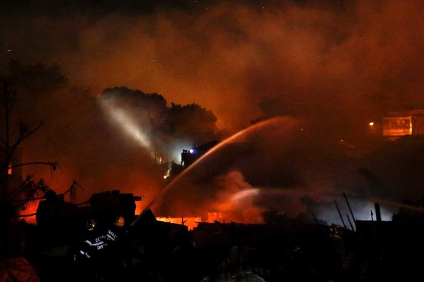 Filipino firemen use water cannon to extinguish a fire in a residential slum area in Quezon City, east of Manila, Philippines, May 6, 2014. T