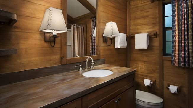 A Contemporary Lodge Style Bathroom Featuring Mirror 2 Wall Sconces Fluffy Towels And Toilet