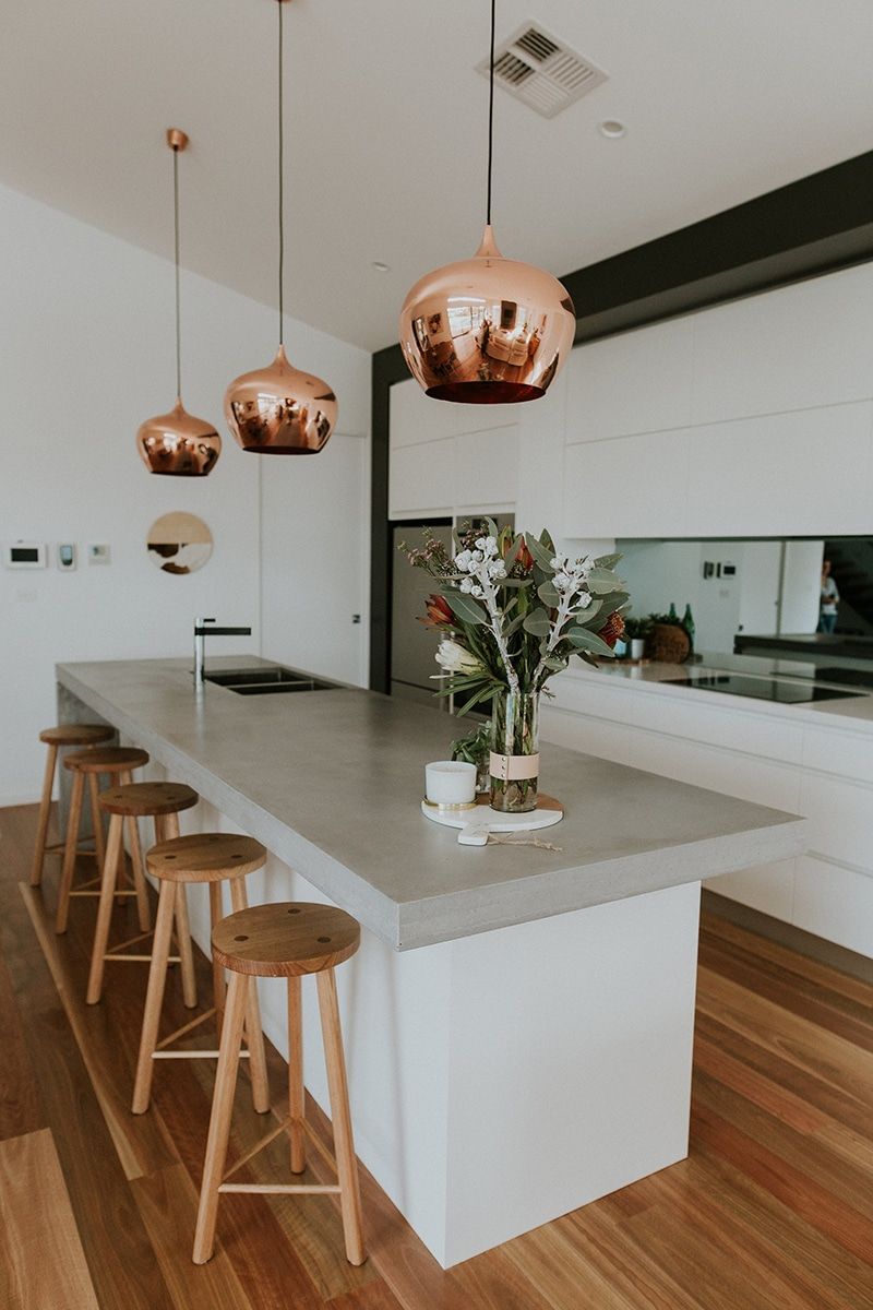 Modern kitchen with a concrete bench top and copper pendant lights