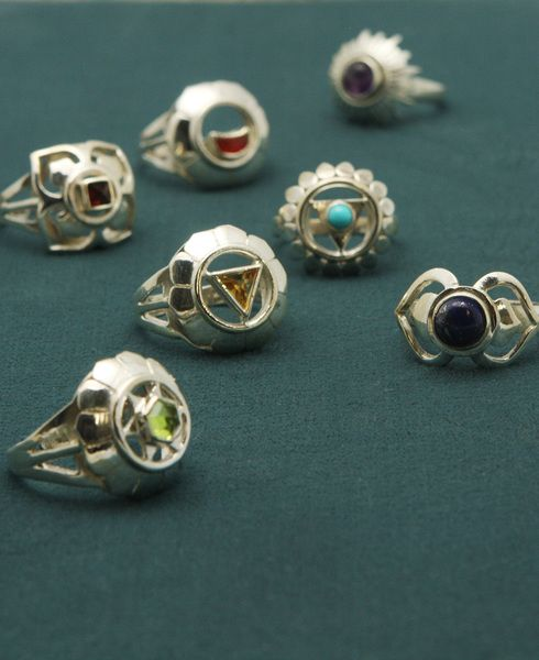 Sterling silver earrings set with colorful gemstones feature symbols representing one of the seven chakras of the body.