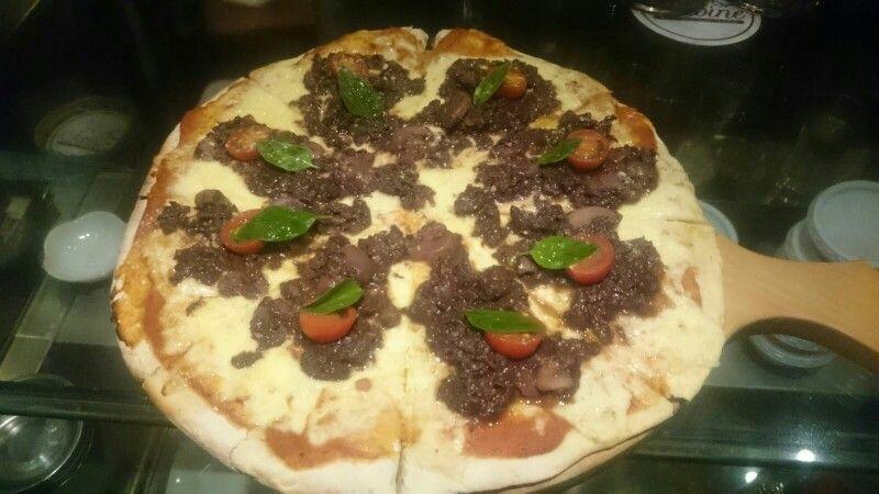 Pizza Osso, a base de mozzarella, pomarola, ossobuco, champiñones, tomates cherry, parmesano y aceite de oliva