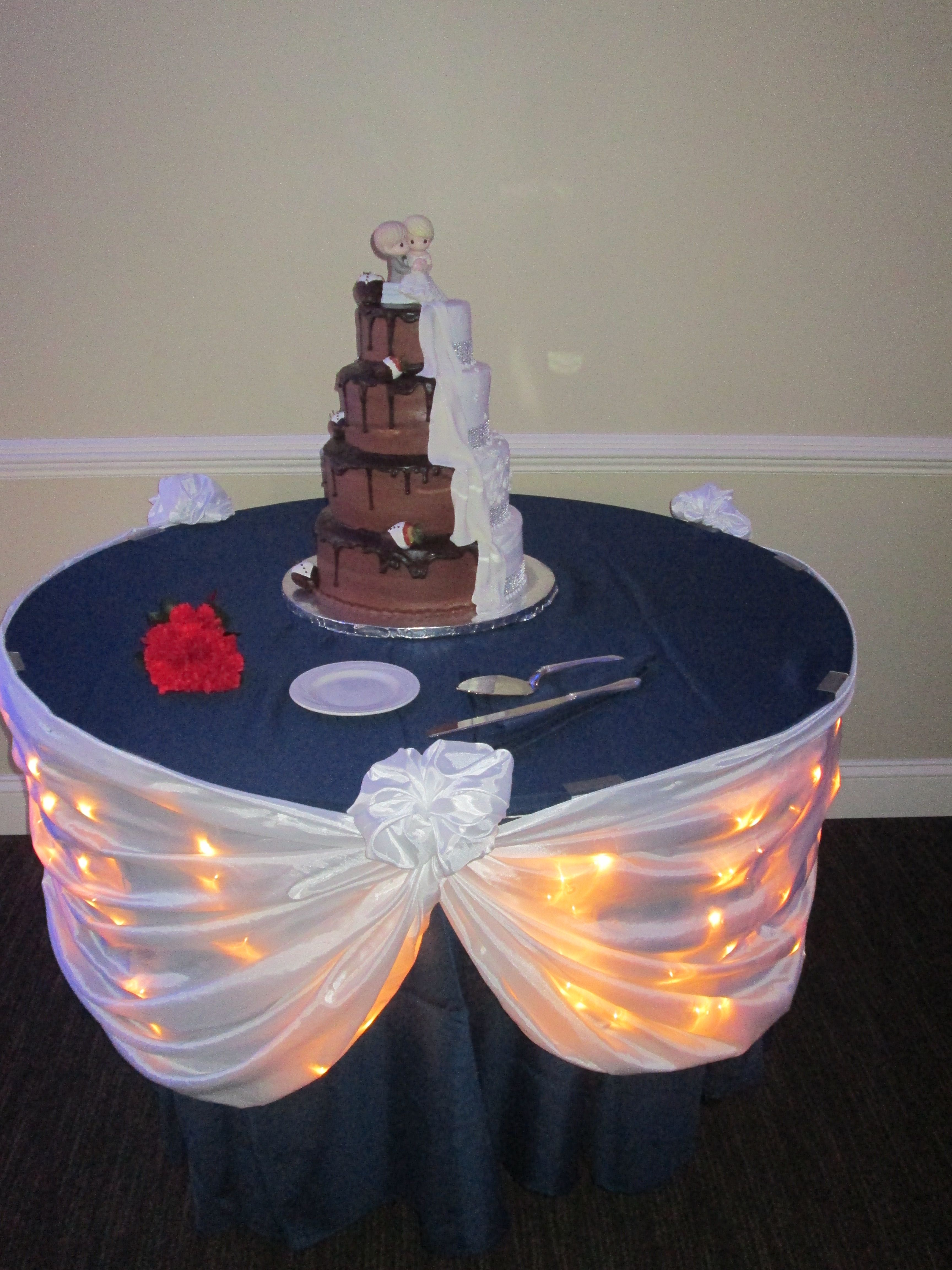 Cake table with lit up white swag on a navy table cloth wedding