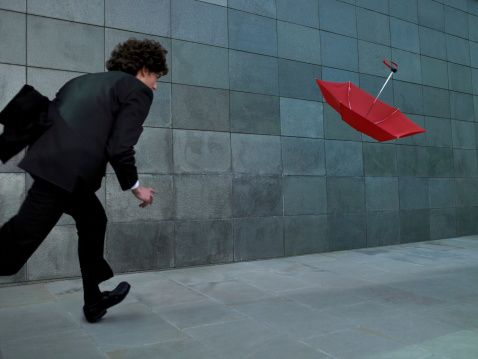 Young Businessman Chasing Umbrella Blowing In Wind Rear View