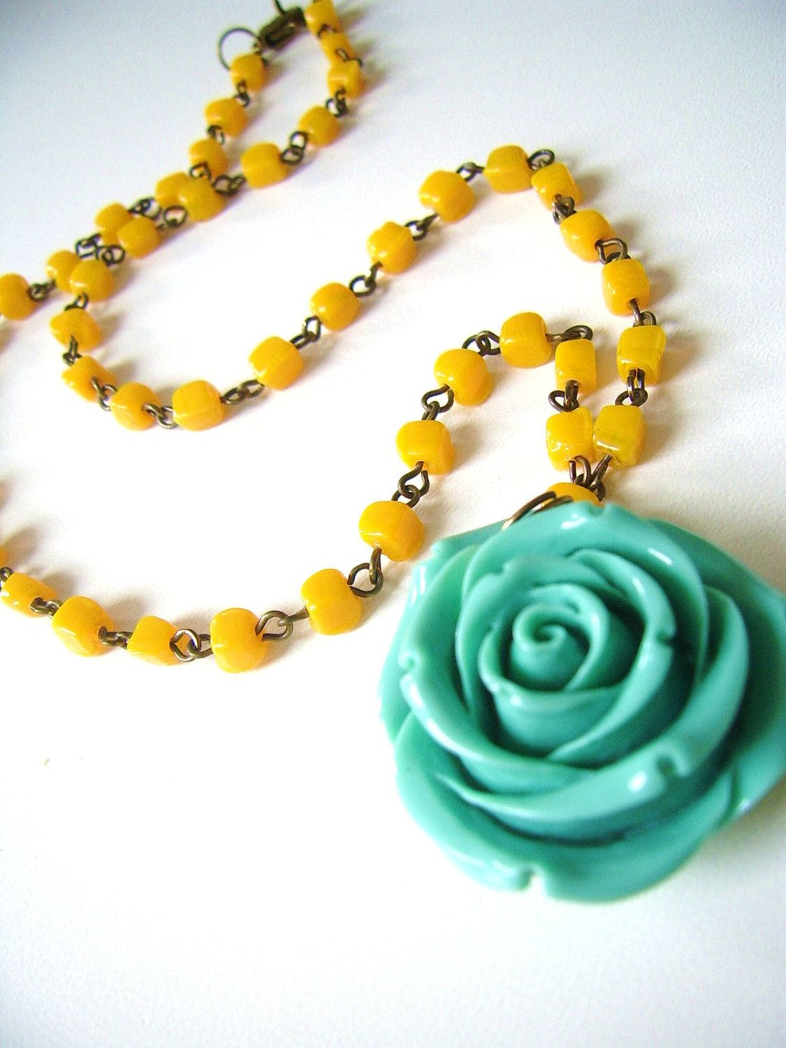 A beaded necklace in honey yellow with big rose pendant honey
