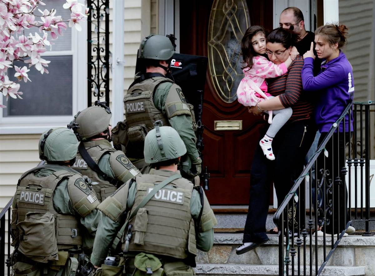 A woman carries a girl from their home as a SWAT team searching for ...