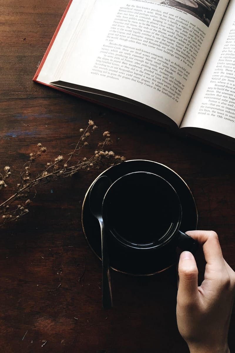 Black Teacup Filled With Coffee Beside Flower and Book