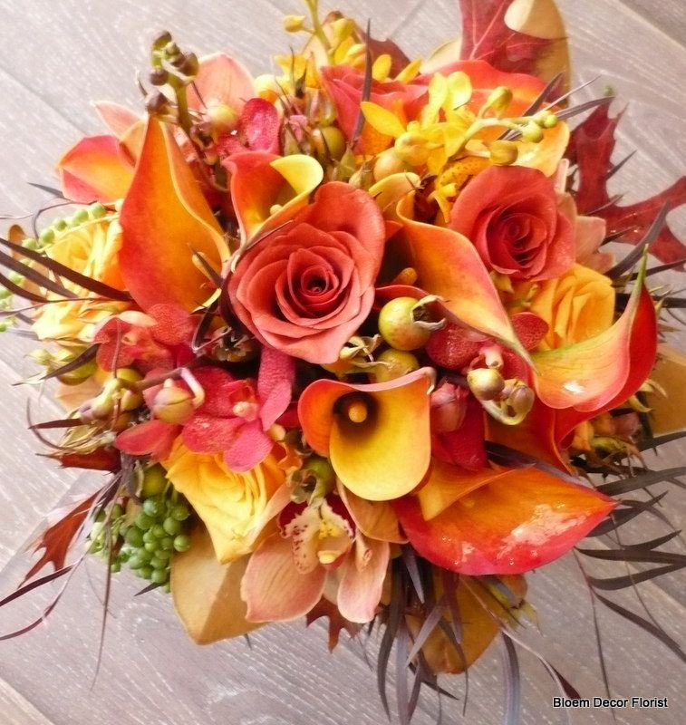 Bridal or bridesmaid bouquet with orange roses, Flame calla lilies, yellow oncidium orchids, hypericum berries and oak leaves.