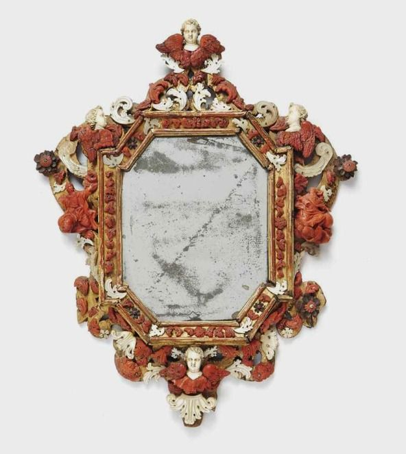 FRAME AND PARTIALLY TILLEUL CARVED GOLD, CORAL, SHELL AND IVORY TRAPANI, OR late seventeenth early eighteenth century Adorned with four heads of winged cherubs carved ivory and coral two figures; the mirror probably later period Height: 37 cm. (14 ½ in.); Width: 30 cm. (11 4/5 in.)
