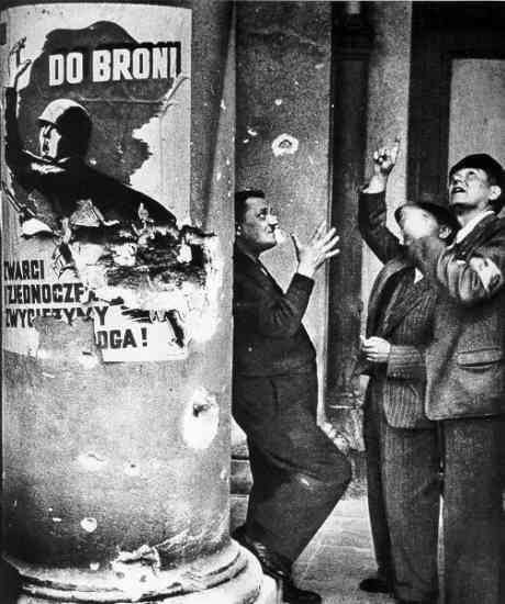 """Volunteer fire-fighters watching an air duel over Warsaw. Propaganda poster reads """"To Arms  United we will defeat the enemy""""."""