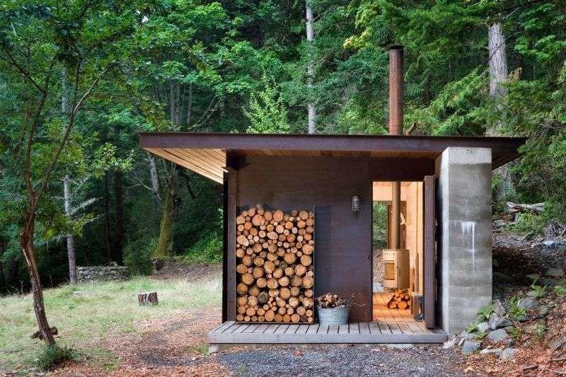 cabane habitable en béton, bois et acier avec rangement pour le bois de chauffage
