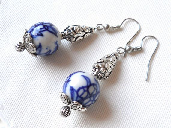 Delft blue dangle earrings made of Delft blue style handpainted porcelain beads (tulips) and silvertone metal beads and bead caps.  The length of the earrings withour the hook is 3.5 cm. (1.4 inches)  For more jewelry please visit our shop: http://www.minouc.etsy.com  For combined shipping please contact us. We also combine shipping with our other Etsy shop where we sell vintage fabrics and finds from Holland and France: http://www.minoucbrocante.etsy.com