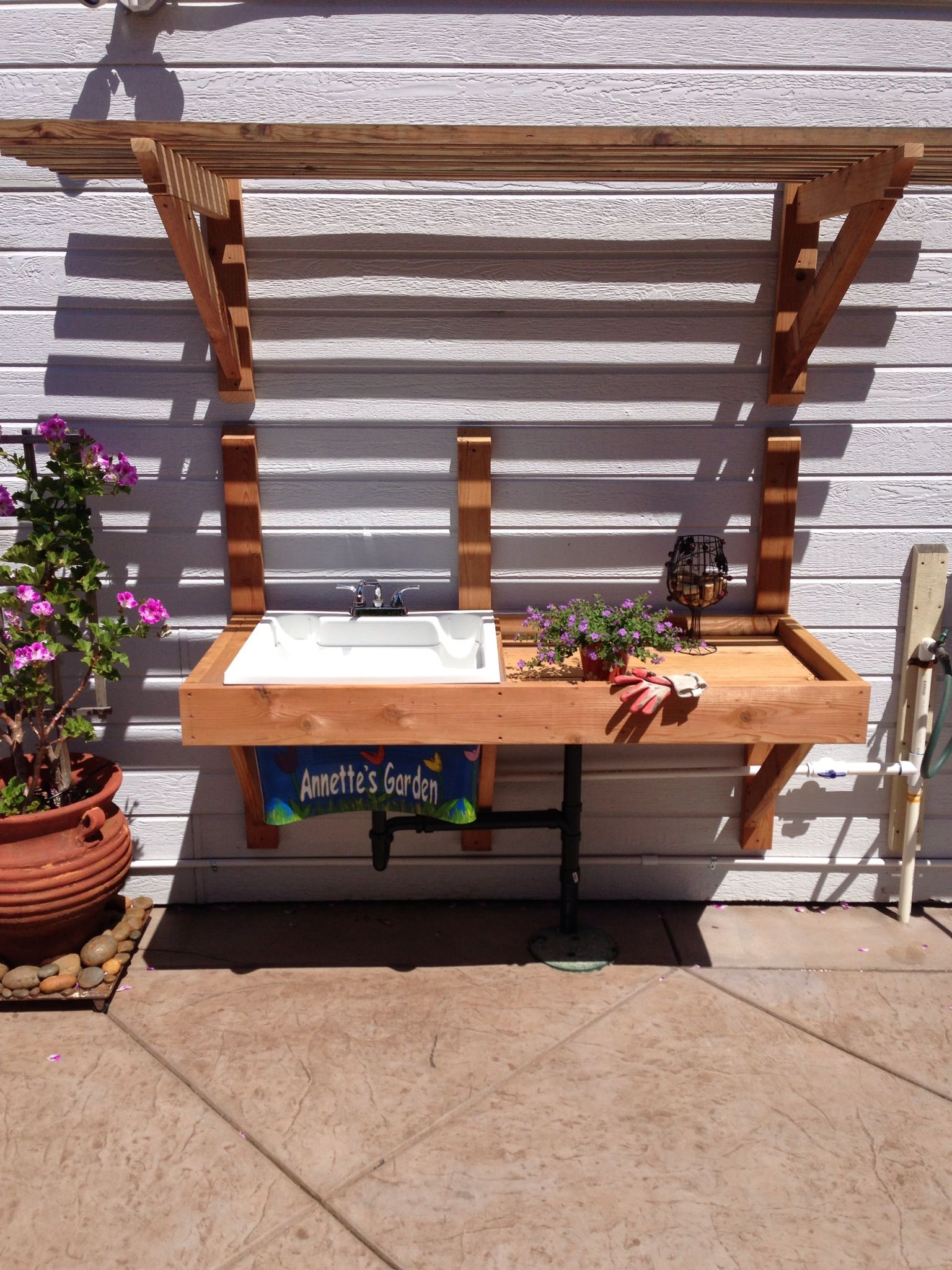Sink attached to outdoor faucet potting table with arbor