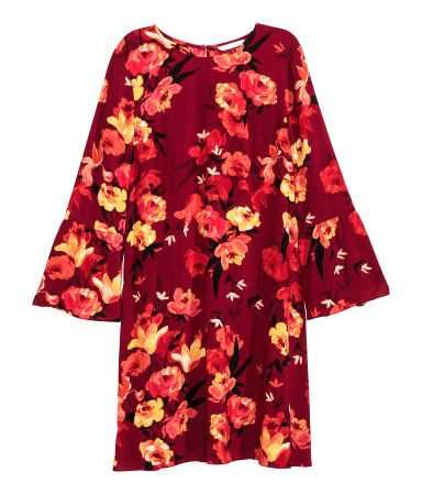 Dark red/floral. Short dress in airy, woven fabric with an opening at back of neck with button, long sleeves with wide flounce at cuffs, and gentle flare to