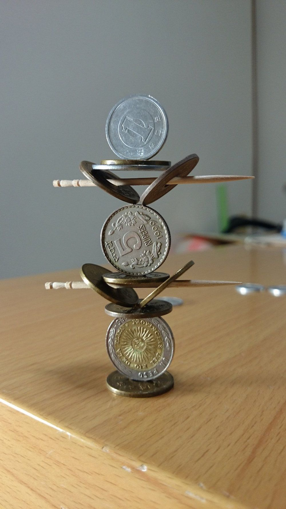 Twitter user stacks coins in impossible ways creating mind-blowing sculptures