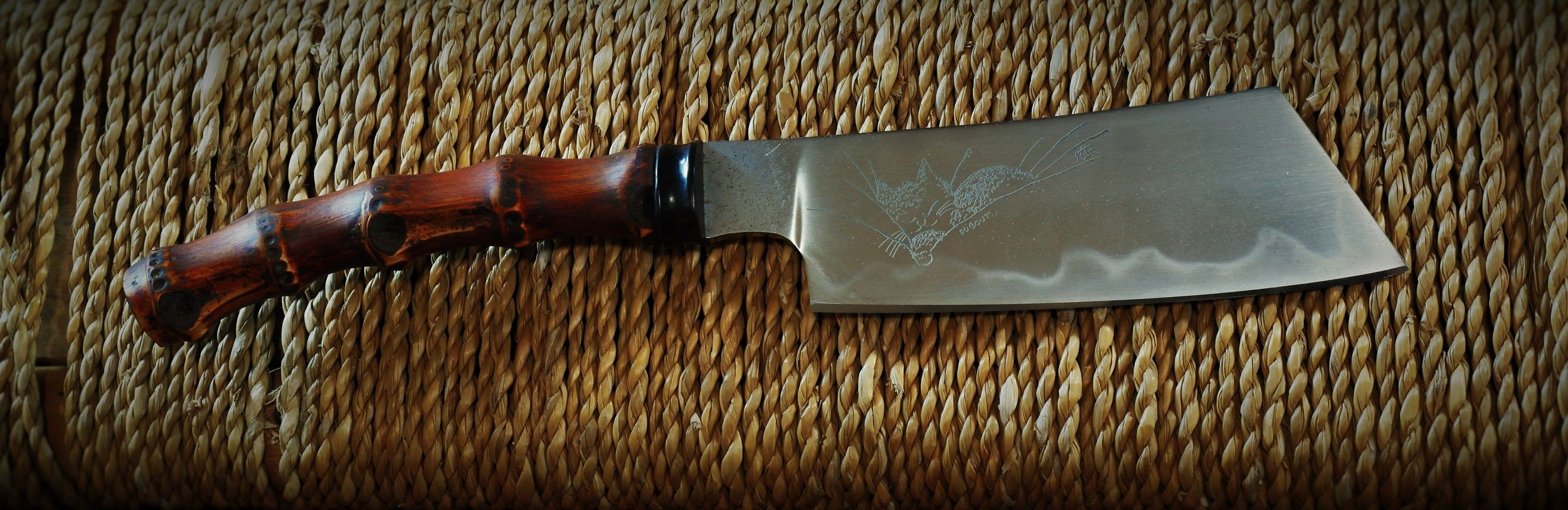 Bamboo root and buffalo horn handle with a clay quenched W2 blade. Engraving based on a drawing by Albert Dubout.