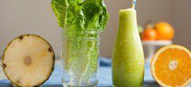 Grüner Smoothie in der Flasche, daneben ein Glas mit Römersalat-Blättern sowie einen aufgeschnittenen Ananas und Orange