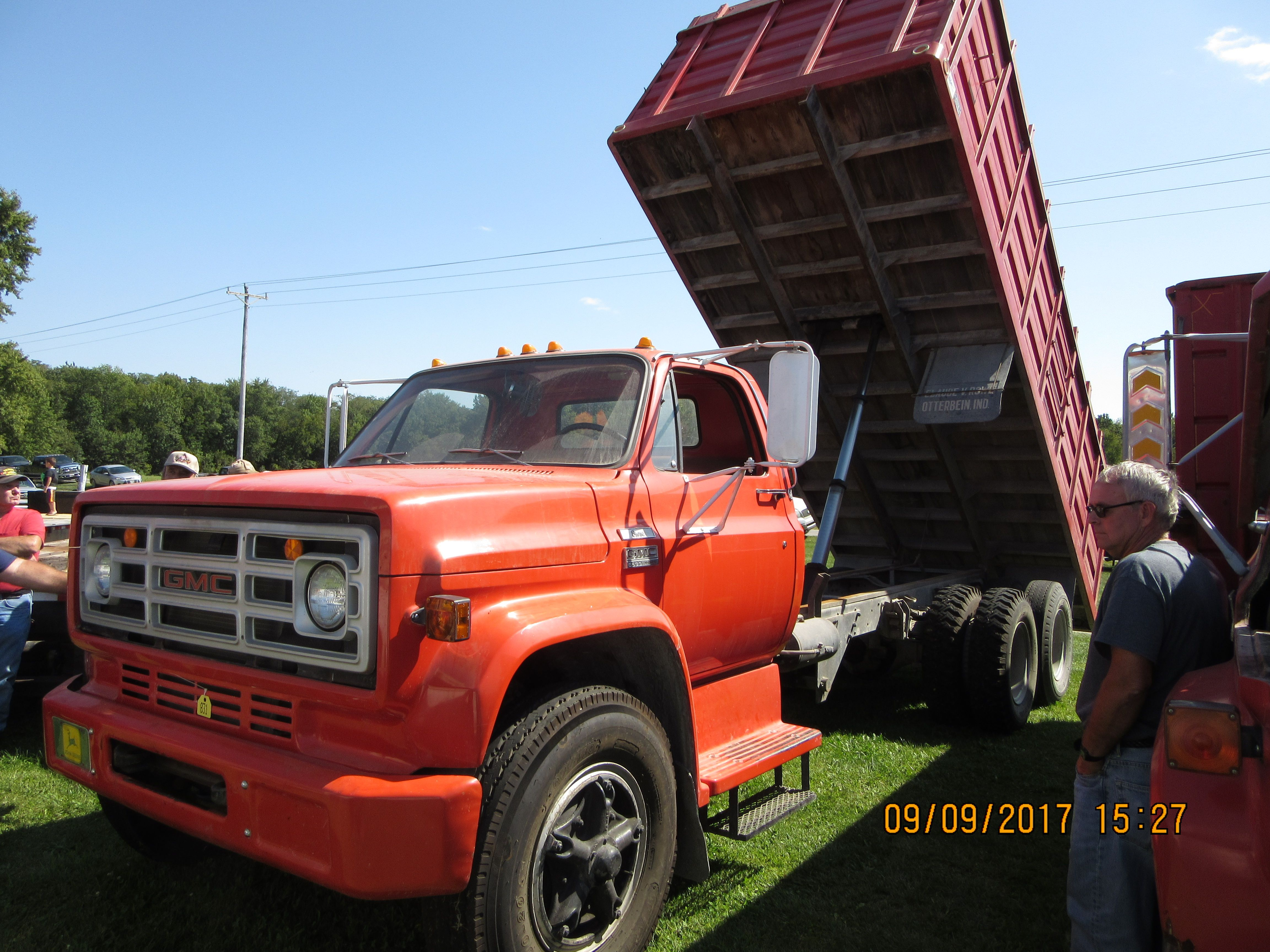 Red GMC 6500 Sierra grain truck with it dump bed up