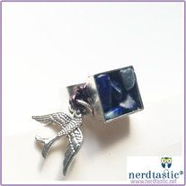 This square pewter ring features lapis sealed with resin in the setting.  Around the outside of the setting is a wire wrapping for the charm to dangle from.  The Tibetan Silver raven is attached with a silver plated pewter jump ring.  The ring is 99.9% fine silver plated pewter (so it's free of...