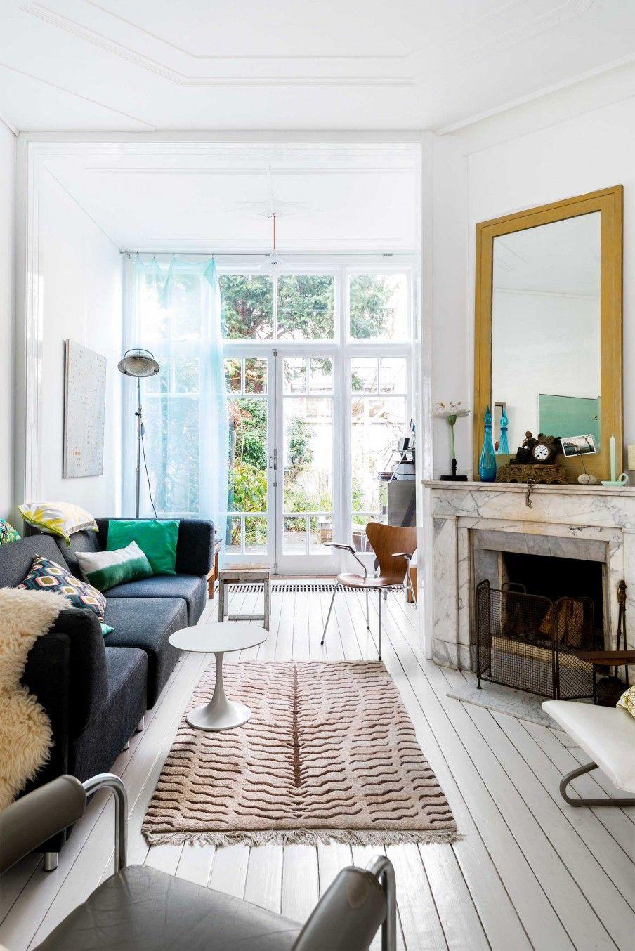Woonkamer met witte vloer en gele spiegel   Living room with white ...