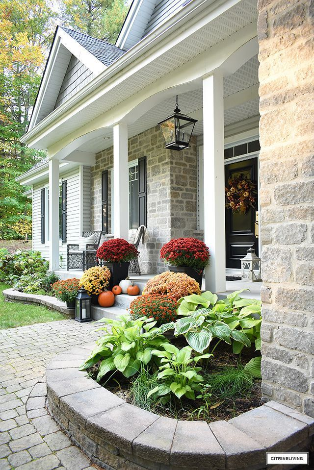 Beautiful fall front porch with lush, colourful mums, scattered pumpkins and a gorgeous wreath welcomes guests for the season. #falldecor #fallhomedecor #fallporch #frontporch #homedecor #homeexterior #homeexteriorideas  #fallwreaths #frontdoor #porchdecor #porchideas #fall