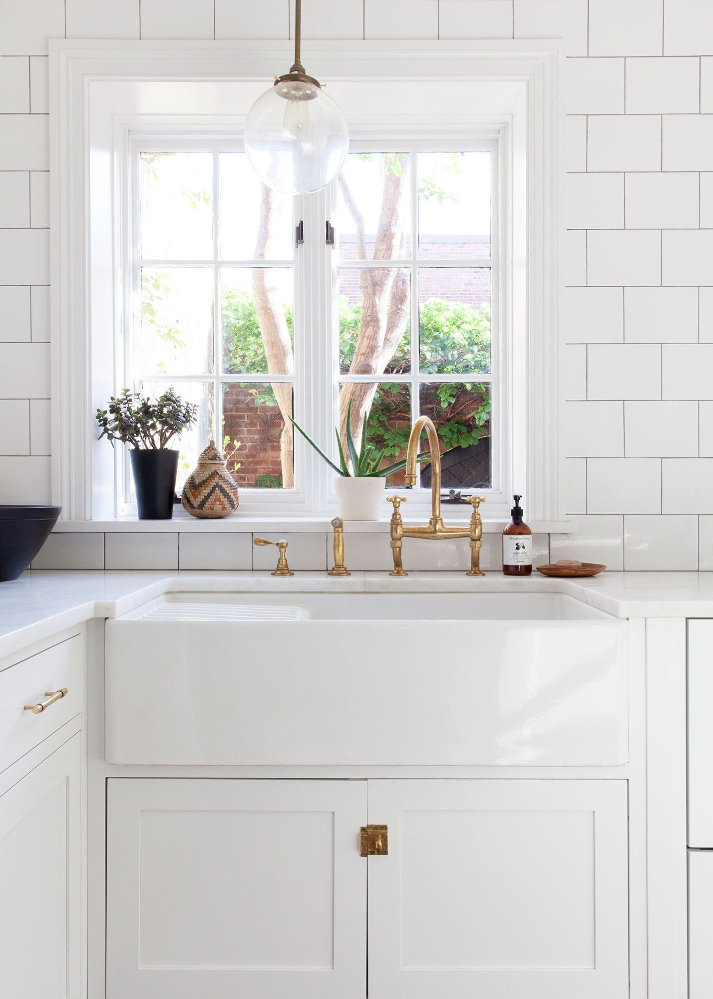A colonial home with a contemporary twist white subway tile white simplicity in the kitchen white cabinetry with a farmhouse sink and white subway tile backsplash i love how the window is slightly offset from the workwithnaturefo