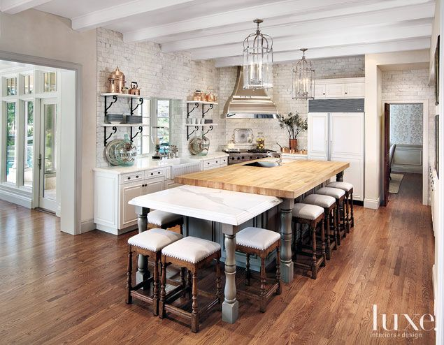 This kitchen's Calcutta marble subway tiles are beveled for added detail. Cabinetry is all custom, and glass and iron lanterns hang over the island. Simple barstools covered in a linen stripe complete the look.