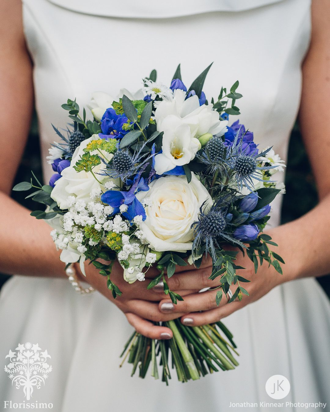 Sinivalkoinen kimppu valkoisista ruusuista, valkoisista freesioista, valkoisista harsokukista, vihreistä krysanteemeista ja sinisistä ritarinkannuksista.