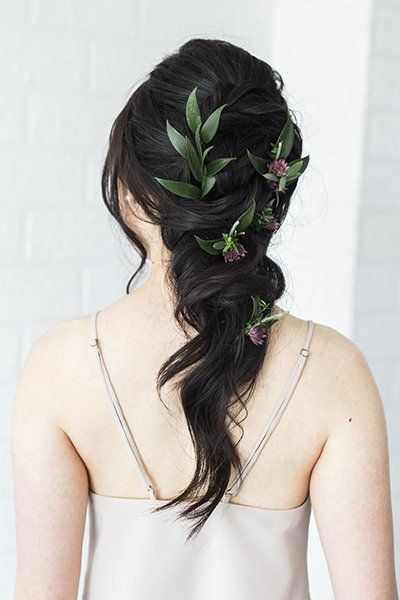 Get creative with a chunky, loose braid dotted with sprigs of greenery.