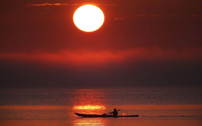 A kayaker paddles near the Frankston foreshore as the sun sets over the low lying cloud of fog in Melbourne Australia