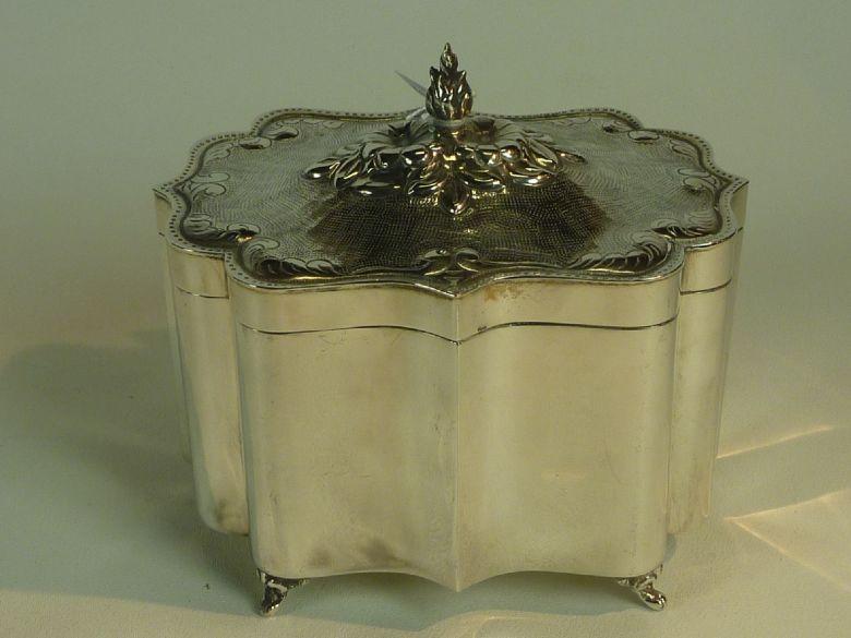 Gecontourneerd zilveren koektrommel met gecicileerde deksel en rustend op pootjes. gew.654 gr.