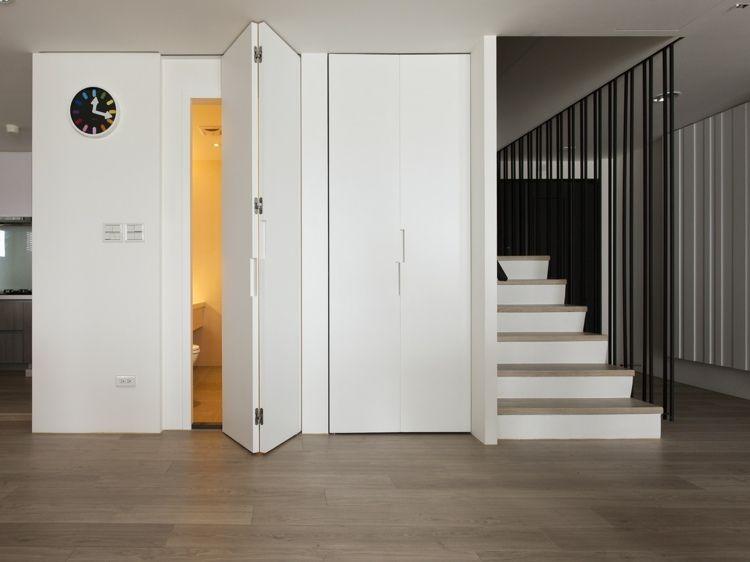eine minimalistische falttür in weiß verschließt das gäste-wc,