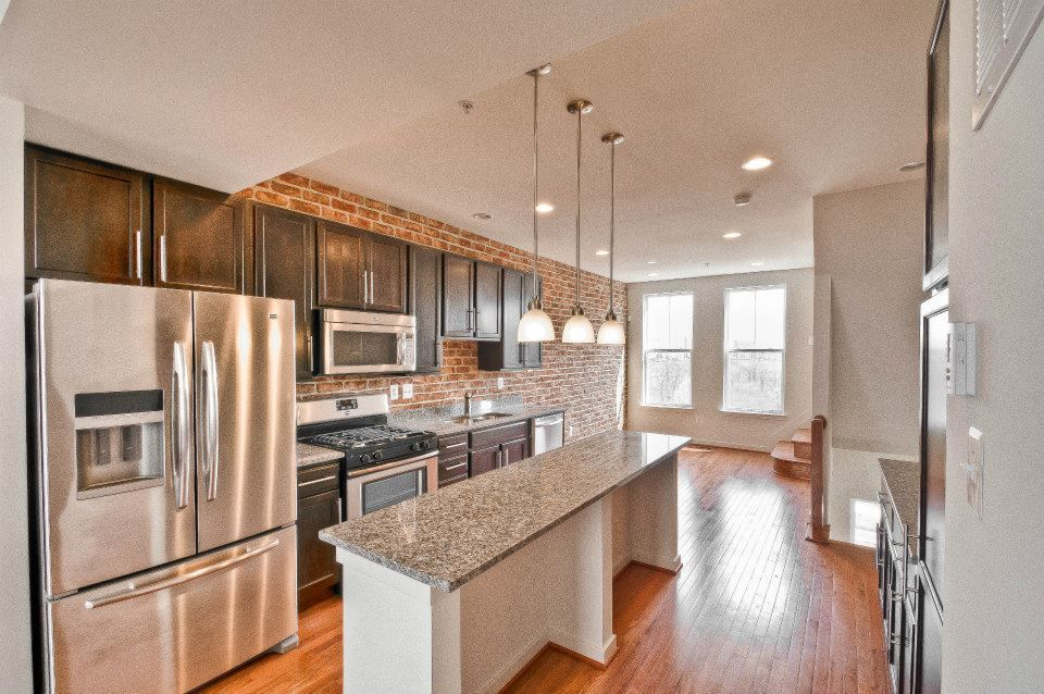 Stainless steel french door refridgerator, natural oak floors, granite countertops, exposed brick, recessed lighting, island. Rowhome in Frederick, MD. Click on picture to see floor plans.