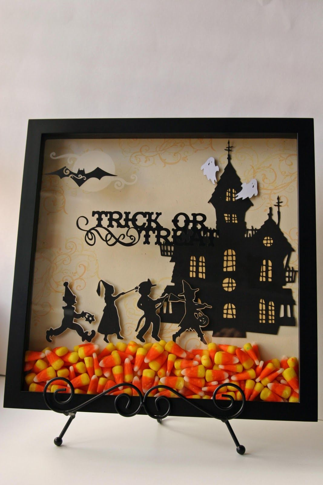 This cute Halloween display was made with a shadow box and a cricut. You could print a scene off the internet or draw your own outline and cut it out of black paper. I love the bright candy corn in the bottom. Great idea to do for any holiday.