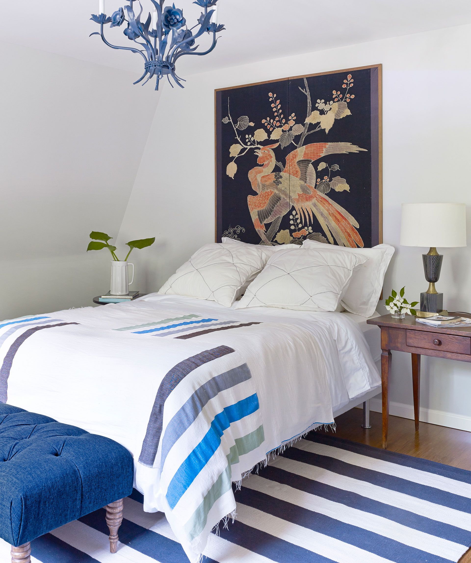 In the guest room of this New York home, a vintage Japanese screen takes the place of a headboard. The Lemlem throw, bench by Garnet Hill, and chandelier (an eBay score) lend hits of blue. Bright idea: A coat of spray paint made an offbeat brass fixture cool.   - CountryLiving.com