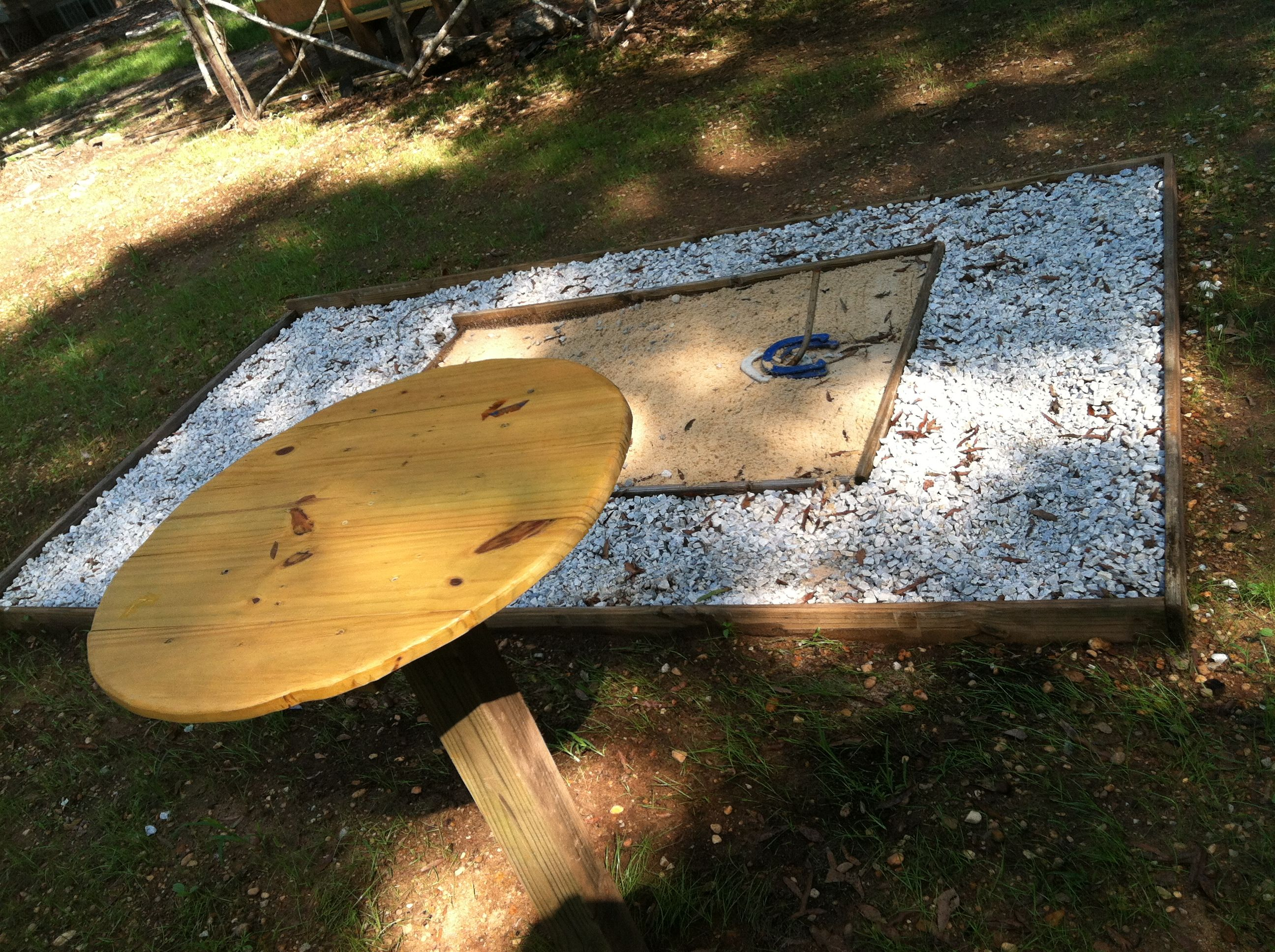 horseshoe pit with a standing table made from scrap wood