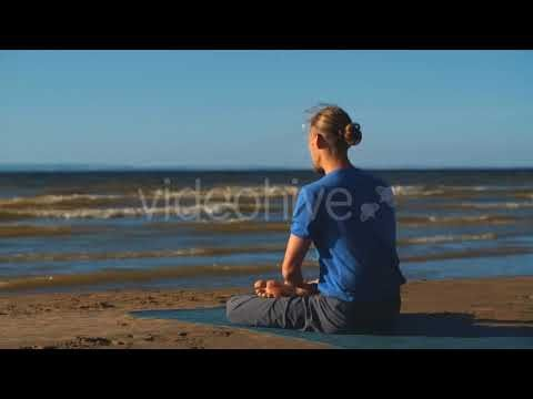 man in lotus pose meditating at the beach stock footage