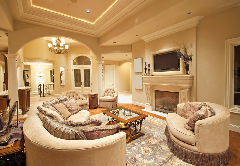 Open Concept Home With Large Living Room As The Center Of It Decorated With  Round Furniture. Room Includes Television And Fireplace.