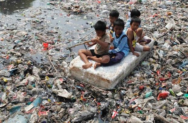 Children Play On A Makeshift Raft In A River Full Of Rubbish In