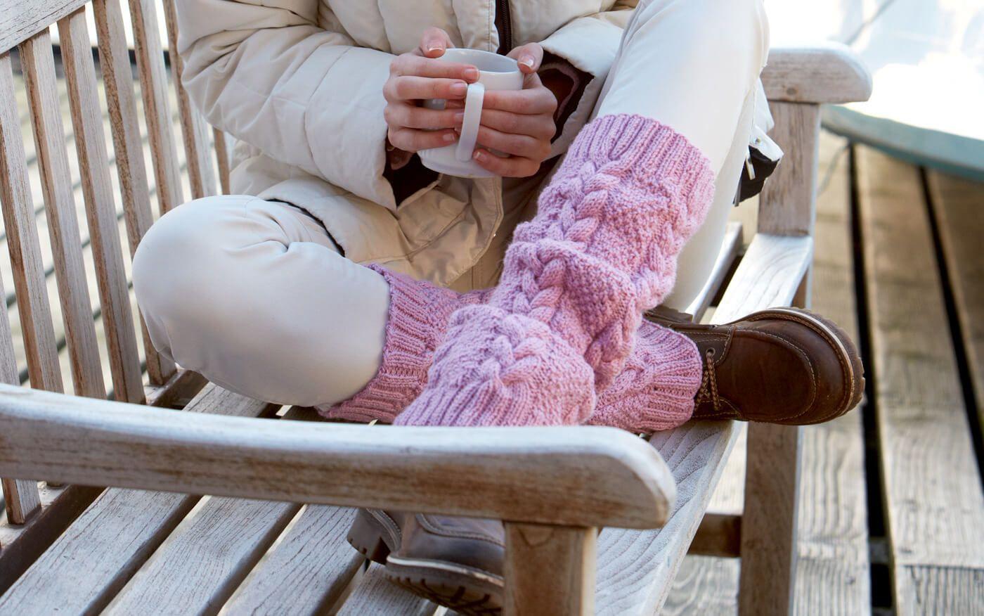Diese traumhaften Beinstulpen in einem Perl- und einem Zopfmuster lassen den Winterschnee und das Hinbeerrosa zu einem Sorbet-Traum verschmelzen.