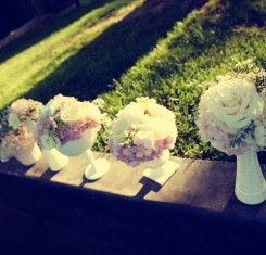 white milk glass containers of pink & white flowers