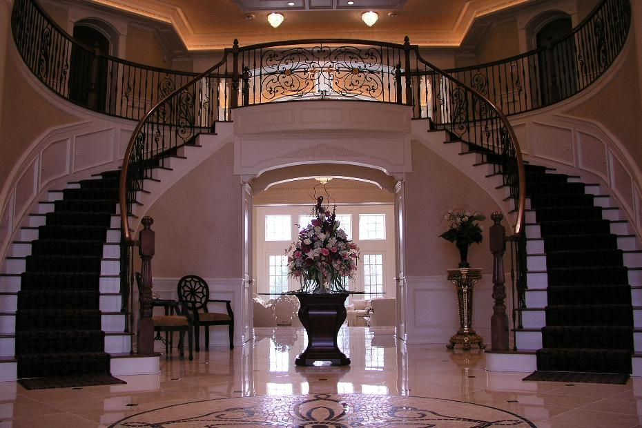 Entryway to a luxury home, with grand staircase and unique tiled ...