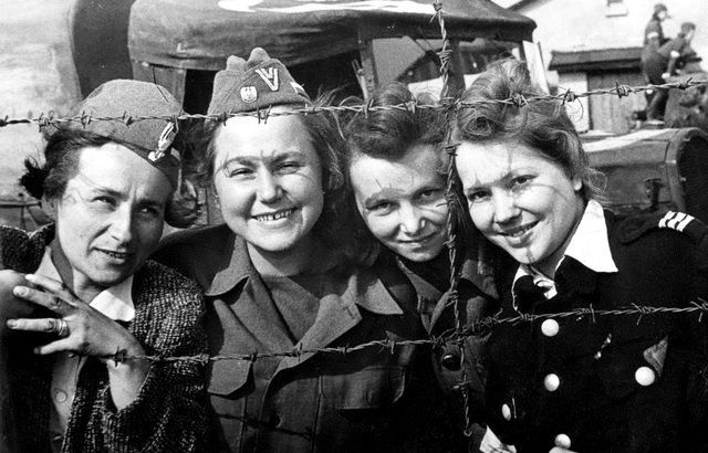 Four Polish insurgents of the Polish Home Army who were captured by Germans after the failed Warsaw Uprising are photographed through barbed wire at Stalag VI-C POW camp after their liberation. April, 1945.