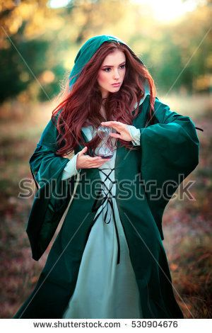 Beautiful Red Haired Girl In Green Medieval Dress In A Hood Holding A Sand Glass And Looking Afar Fairy Tale Sto Medieval Dress Red Curly Hair Fantasy Clothing