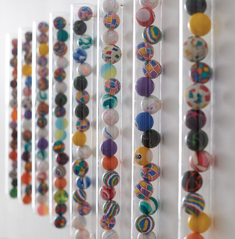 Bouncy Balls In Narrow Plastic Tubes Affixed To A Wall.