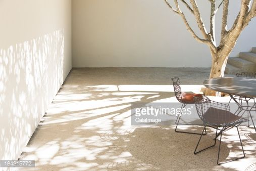 Table and chairs casting shadows in courtyard